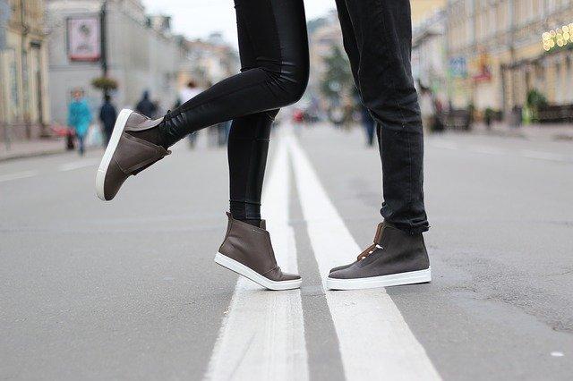 Füße die an einer Strassentrennlinie stehen und eine Grenze symbolisieren