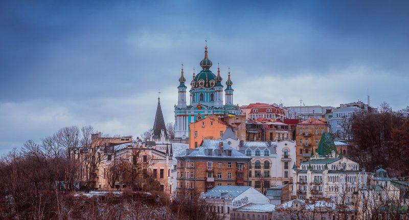 Blick auf Kiew vor wolkigem Himmel mit schönen bunten alten Gebäuden